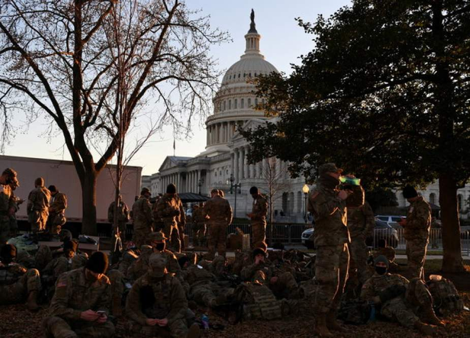 National Guard troops rest on a yard in front of the US Capitol.JPG